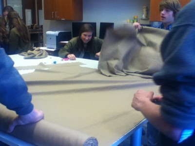 Students cut multiple layers of linen for the armor project.