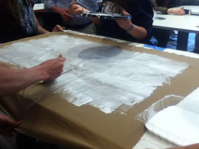 Students spread glue on the first layer of fabric.